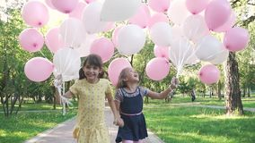 Two little girls gleefully run through the summer the Park with balloons in his hands. little sisters holding hands and. Children run through the Park with a stock video