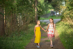 Two little girls go for the handle on the green alley. Walking. Royalty Free Stock Images