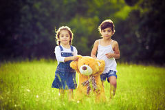 Two little girls in the grass with teddy bear Royalty Free Stock Photo