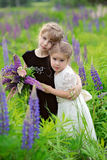 Two little girls at the green field in sunset time, with bouquet. Two little girls in black and white dresses with bouquet at the green field with violet flowers Royalty Free Stock Image