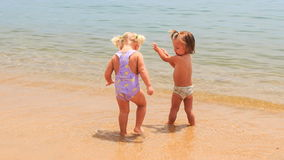 Two little girls with hairtails play with wave in seawater. Two little blonde girls with hairtails in swimsuits play with wave on edge of shallow seawater on stock footage