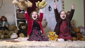 Joyful sisters in a room with plush toys, slow motion. Two little girls happily shout and wave their hands sitting on a nap white carpet stock video