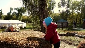 Two little girls having fun on haystack. They jump and climb onto it. Slow motion stock video footage