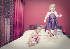 Two little girls having fun while jumping on a bed Royalty Free Stock Images