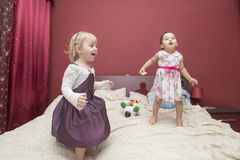 Two little girls having fun while jumping on a bed Stock Photos