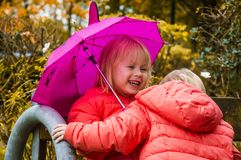 Moment of happiness! Happy little girls with umbrellas on a sunny autumn day after the rain, children in bright jackets in the par stock image