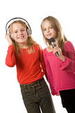 Two little girls with headphones and microphone Royalty Free Stock Photo