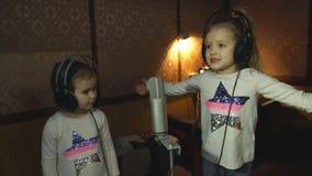 Two little girls in headphones singing in microphone. Two little girls in headphones singing into microphone in recording Studio stock video