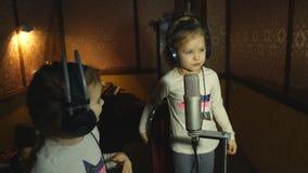 Two little girls in headphones singing in microphone. Two little girls in headphones singing into microphone in recording Studio stock footage
