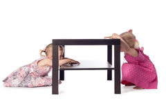 Two little girls hiding behind table Royalty Free Stock Photos