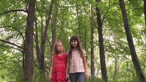 Two little girls hold hands and walk down the green alley. Children walk outdoors. two little sisters stock video footage