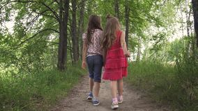 Two little girls hold hands and walk down the green alley. children walk outdoors. two little sisters.  stock video