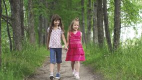 Two little girls hold hands and walk down the green alley. Children walk outdoors. Two little sisters. Slow motion stock video
