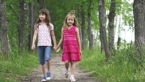 Two little girls hold hands and walk down the green alley. children walk outdoors. two little sisters. slow motion stock video footage