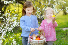 Two little girls holding a basket of Easter eggs Stock Images