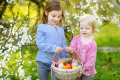 Two little girls holding a basket of Easter eggs Stock Photos