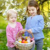 Two little girls holding a basket of Easter eggs Royalty Free Stock Photo