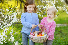 Two little girls holding a basket of Easter eggs Stock Photo