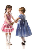 Two little girls holding hands stock images