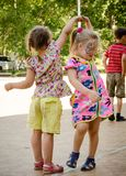 Two little girls holding hands dancing on a city holiday stock photography