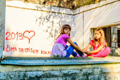 Two little girls holding hands. Two little girls are sitting on the old window opening and are holding hands Royalty Free Stock Photo