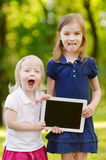 Two little girls holding tablet PC outdoors Stock Images