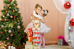 Two little girls hugging each other in a Christmas setting Stock Images