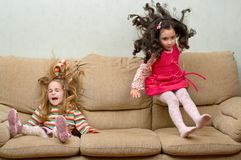 Two little girls jumping on sofa royalty free stock images