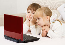 Two little girls are with a laptop. And a credit card Royalty Free Stock Image