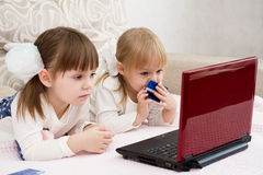 Two little girls are with a laptop. And a credit card Royalty Free Stock Photography