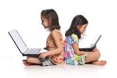 Two little girls with laptop computers. Isolated on a white background Royalty Free Stock Images