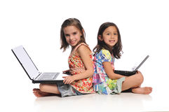 Two little girls with laptop computers. Isolated on a white background Royalty Free Stock Photo