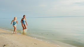 Two little girls laughing on the beach - running along the water`s edge stock footage