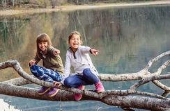Two little girls laughing and pointing fingers on Lake Biograd ( Stock Photo