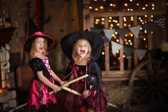 Two little girls laughing witch on a broomstick. childhood Hallo Stock Image