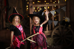 Two little girls laughing witch on a broomstick. childhood Hallo Royalty Free Stock Photos