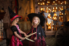 Two little girls laughing witch on a broomstick. childhood Hallo Stock Photos