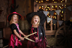 Two little girls laughing witch on a broomstick. childhood Hallo Royalty Free Stock Image