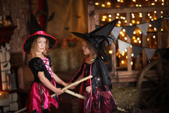 Two little girls laughing witch on a broomstick. childhood Hallo Stock Photography