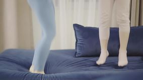 Two little girls in leggings jumping on a king size bed, fast. Legs of two little girls preschoolers or school students jumping on their parent s bed with a blue stock footage