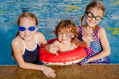 Two little girls and little boy playing in the pool Stock Photography
