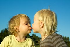 Two little girls. Two little  lovely girls give kiss outdoor Stock Image