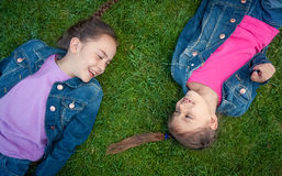 Two little girls lying on grass face to face and laughing Royalty Free Stock Photo