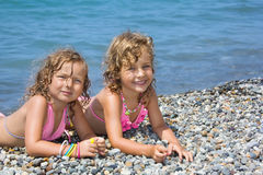 Two little girls lying on stony beach Royalty Free Stock Photo