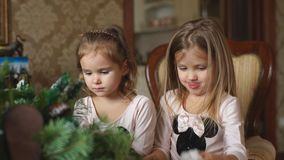 Two little girls make a Christmas wreath. With grandmother stock video