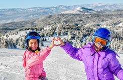 Two little girls making heart with their hands in the snow Stock Images
