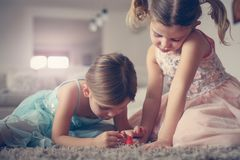 Sisters painted nails together.Two little girls. Two little girls nailed their nails at home. Close up image two little girls have play with mothers nail polish Stock Images