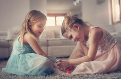 Sisters painted nails together. Two little girls at home. Two little girls nailed their nails at home. Smiling and happy little girls Stock Images
