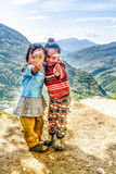 Two little girls in Nepal holding flowers in their hands Stock Photos