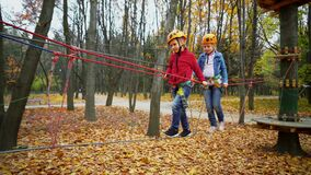 Two little girls in orange helmets and protective gear on rope-way in autumn  forest. Children are engaged climbing rope park.